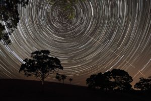 "The International Space Station appears to pierce a path across the radiant, concentric star trails seemingly spinning over the silhouettes of the trees in Harrogate, South Australia. Highly Commended in the ""Young Astronomy Photographer"" category. Image: Scott Carnie-Bronca"