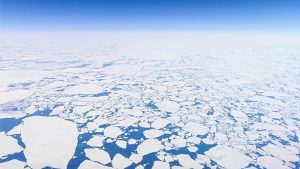 Aerial photo of the endless Arctic ice sheet just off Greenland's west coast, close to the Polar circle. The sheet is broken up in millions of pieces, forming a scattered pattern of white against a dark blue Atlantic ocean and sky. Photo taken from the cockpit of an airliner flying at an altitude of 12 kilometers.