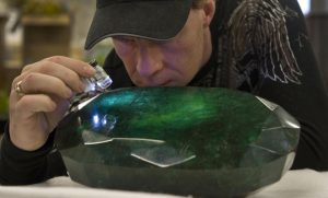 "Regan Reaney, owner of the the world's largest emerald looks over the gem at the Western Star Auction House in Kelowna, British Columbia January 26, 2012. The 57,500 carat emerald, named ""Teodora"", which weighs 11.5 kg (25.35 lb) was mined in Brazil and cut in India. The stone will be publicly auctioned this weekend. REUTERS/Andy Clark (CANADA - Tags: SOCIETY TPX IMAGES OF THE DAY)"