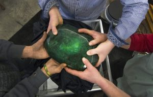 "People hold the world's largest emerald at Western Star Auction House in Kelowna, British Columbia January 26, 2012. The 57,500 carat emerald, named ""Teodora"", which weighs 11.5 kg (25.35 lb) was mined in Brazil and cut in India. The stone will be publicly auctioned this weekend. REUTERS/Andy Clark"