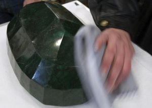 "A worker polishes the world's largest emerald at Western Star Auction House in Kelowna, British Columbia January 26, 2012. The 57,500 carat emerald, named ""Teodora"", which weighs 11.5 kg (25.35 lb) was mined in Brazil and cut in India. The stone will be publicly auctioned this weekend. REUTERS/Andy Clark"