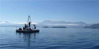 Researchers taking sediment cores on Chilean lake Calafquén (with Villarrica Volcano in the background).