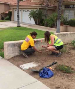 LSU's Patricia Persaud (left) and a Cal Tech undergraduate student mark a newly-buried geophone node in a Los Angeles yard.