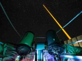 The experiment on La Palma: The laser beam (yellow) generates an artificial guide star in the mesosphere. This light is collected in the receiver telescope (front left). The laser source and the receiver telescope are eight meters away from each other. Credit: Copyright Felipe Pedreros Bustos