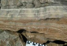 Field photograph of massive flowstone layers from one of the South African hominin caves, with red cave sediments underneath.