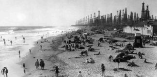 Angelenos play below derricks at Huntington Beach pier, c. 1930-40. In the early decades of the twentieth century, LA residents accepted ground subsidence and small earthquakes as the cost of producing oil. But discontent began to rumble in the late 1930s. Rapid exploitation of Wilmington, one of the largest oil fields in California, and the Huntington Beach field caused Long Beach harbor to sink, buckling railway lines and forcing the city to build higher piers. Credit: Orange County Archives