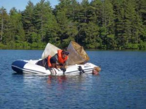 Doctoral students Daniel Miller, in the water, with Helen Habicht and Benjamin Keisling, handle two recaptured sediment traps from an unusually deep lake in central Maine, where they collected 136 sediment samples spanning the 900-year time span to reconstruct the longest and highest-resolution climate record for the Northeastern United States to date.
