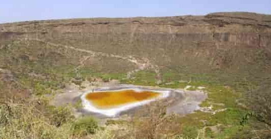 Explosive volcanic crater (maar) with small lake at the bottom close to Dilo