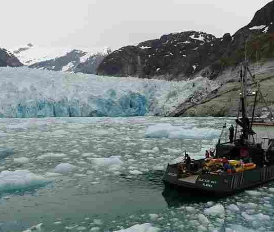 Researchers on the MV Steller are in front of the terminus of Alaska's LeConte Glacier in August 2016. An over-the-side pole holds the sonar instrument that collects data on the subsurface ice face as the vessel moves slowly through the icy water. Credit: David Sutherland