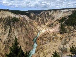 A river flows between mountains at Yellowstone National Park in Wyoming. New research tests a 30-year-old theory on the relationship between erosion and mountain height. Photo credit: Seth Cottle/Unsplash