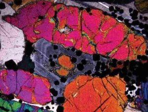 Photomicrograph in crossed polars of precious-metal bearing peridotite. Note the optical zoning (light/dark bands) in the plagioclase (grey coloured mineral) in the central part of the image. The occurrence of this zoning was the focus of the study in question. The width of the image frame is 4 mm. Credit: Nat. Geosci. (2020).