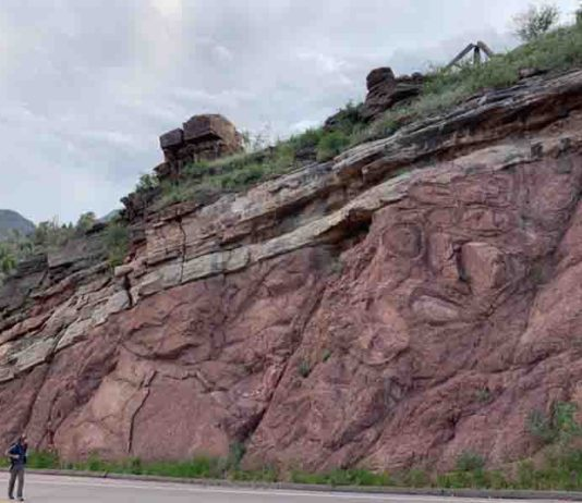 """Francis Macdonald walks along a road near Manitou Springs, Colorado, where an exposed outcrop shows a feature known as the """"Great Unconformity."""""""