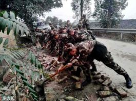 Soldiers remove bricks from the road after earthquake in Rongxian county on 25 February 2019.   Credit: IC