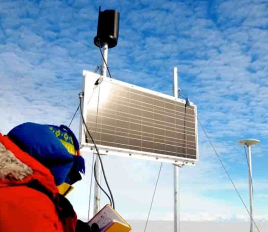 Matthew Siegfried inspects a GPS device, powered by a solar panel at Whillans Ice Plain. Credit: Grace Barcheck/Cornell University
