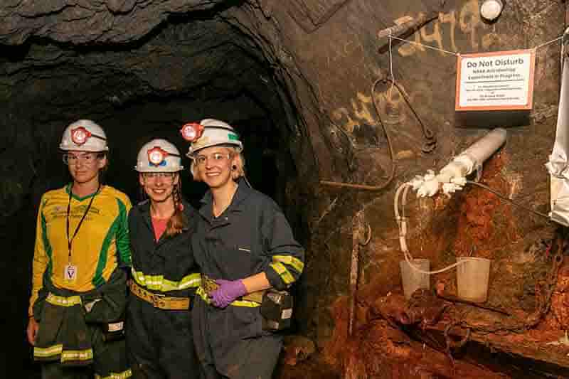 DeMMO field team from left to right: Lily Momper, Brittany Kruger, and Caitlin Casar sampling fracture fluids from a DeMMO borehole installation. Credit: ©Matt Kapust