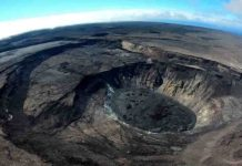 A wide-angle aerial view looks southeast over Kīlauea's summit caldera on July 22, 2021. Large cliffs formed during the 2018 collapses are visible on the left side of the photo. A recently active lava lake is visible in the lower right. (Image credit: M. Patrick, USGS)