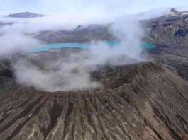 The rim of Cone D—inside the Okmok Volcano caldera—with the blue lake in the background. Credit: Nick Frearson